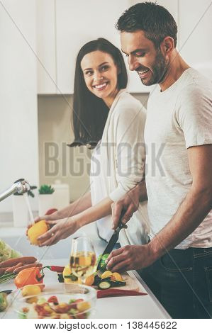 Cooking with pleasure. Beautiful young loving couple cooking together while standing in the kitchen