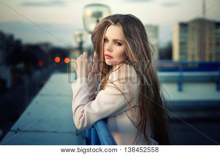 Beautiful lonely young pretty girl standing on the city roof in the sunset. Sensual evening portrait.