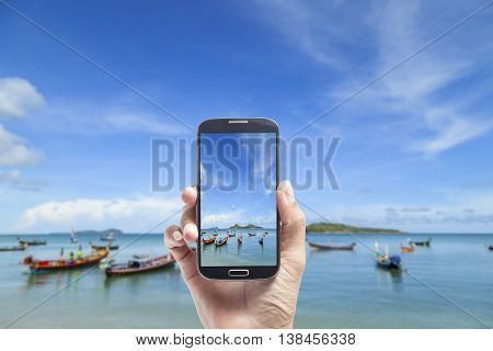 hand male Asian holding smartphone taking picture of beautiful beachand sea blue sky background
