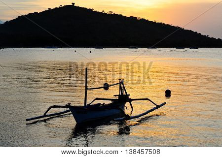 Sunset view from the sea in the West bali together with a traditional Balinese fishing boat on foreground