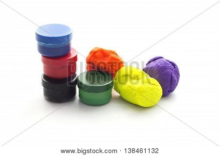 Three Modelling clay balls and filger painting of different colors isolated on a white background