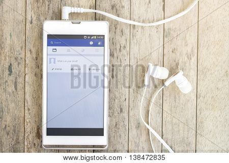 BUNG KAN THAILAND - MARCH 22 2016: smart phone display facebook app with earphones on wood background with sunlight