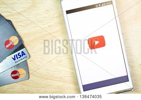 BUNG KAN THAILAND - JANUARY 20 2016: smart phone display youtube app and credit card on table smart phone selective focused with sunlight