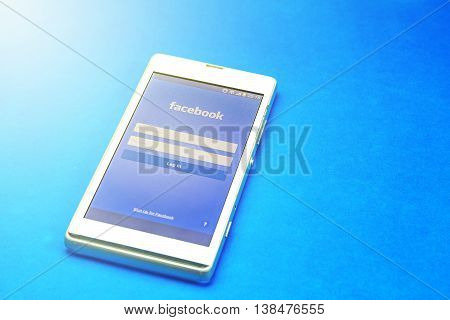 BUNG KAN THAILAND - JANUARY 29 2016: smart phone display facebook app on blue background with sunlight soft focused