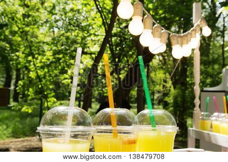 Lemonade in plastic cup on the fair of festival street food. Garland fair bulbs. Summer refreshing drink lemonade. Plastic cup you can take with.