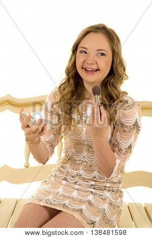 a girl with down syndrome in her vintage dress putting on her make up with a smile.