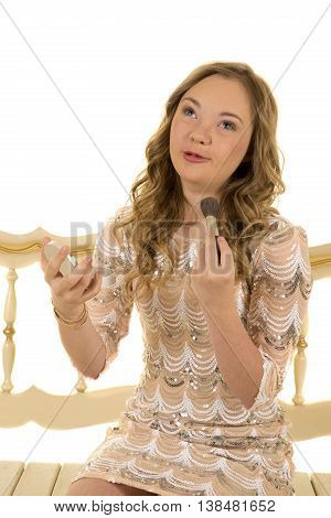 a girl with down syndrome sitting on a bench putting her makeup on her face with a cute expression.