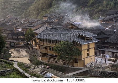 Zhaoxing Dong Village Guizhou Province China - April 8 2010: Twilight in the village of Dong ethnic minority steam rises from the tiled roofs of wooden houses highlands spring.