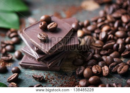 Stack of chocolate chunks with coffee beans on a wooden background closeup