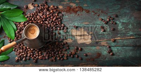 Hot coffee in a coffeepot or turk on a wooden background with coffee leaves and beans horizontal with copy space. Top view