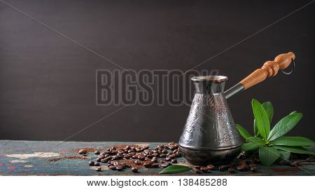 Hot coffee in a coffeepot or turk on a wooden background with coffee leaves and beans horizontal with copy space