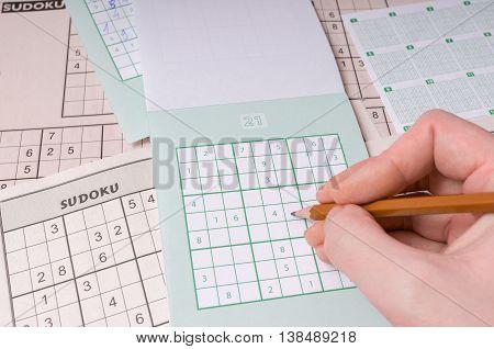 Popular Brain Teaser Logic Game Sudoku. Hand Is Writing Numbers