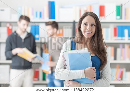 Confident smiling student girl posing in the library holding notebooks and looking at camera learning and education concept