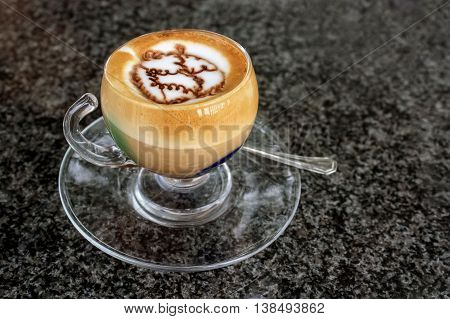 A cup of a special art of coffee marocchino in a glass cup on the dark table.