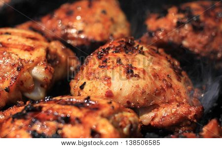 Delicious chicken thighs are being cooked with seasoning and sauce on charcoal grill with smoke rising from hot coals