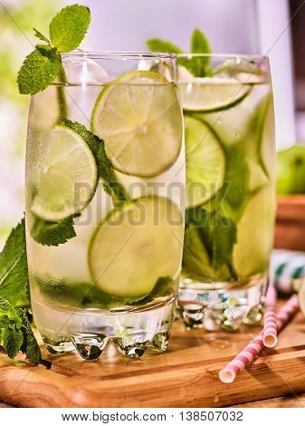 Alcohol drink. On wooden boards two glasses alcohol drink and ice cubes. Close up of drink number hundred fifty seven cocktail mohito with straw and lime and mint leaf. Country life. Light background.
