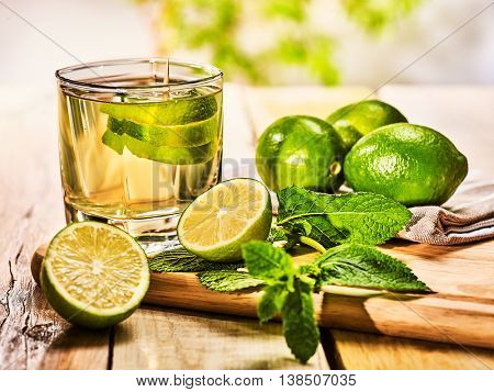 Alcohol drink. On wooden boards glass with alcohol green mohito drink. Mint drink number hundred fifty four mojito cocktail with half lime and napkin. Country still life outdoor. Light background.