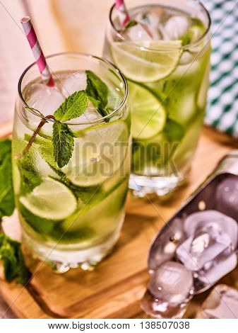 Alcohol drink. On wooden boards three glasses with alcohol drink and ice cubes. Drink number hundred fifty nine cocktail mohito and scoop ice with straw. Country mohito cocktail. Light background.