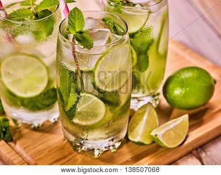 Alcohol drink. On wooden boardsthree glasses with alcohol cocktail drink and ice cubes. Drink hundred sixty one cocktail mohito and cube ice with straw. Country life. Top view. Light background.