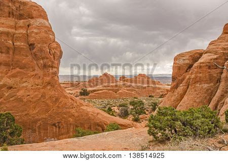 View from Devils Garden area of Arches National Park with dark clouds trying to send rain to the desert