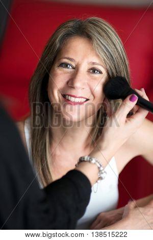 Beautician Applying Blusher To A Young Woman