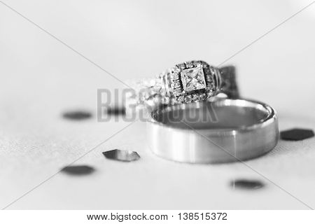 Black and white image of wedding rings on table.