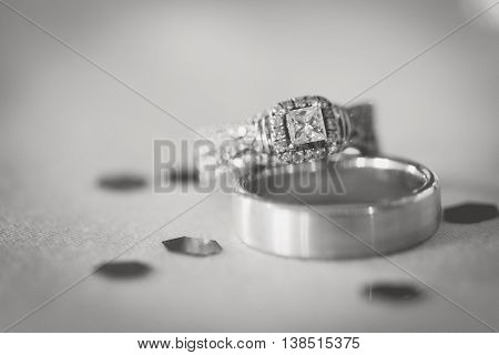 Black and white image of wedding rings with glitter.