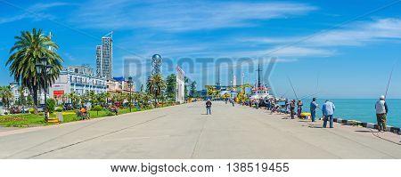 BATUMI GEORGIA - MAY 25 2016: The seaside promenade with beautiful ornamental garden moored longboats and many fishermen on May 25 in Batumi.