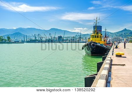 BATUMI GEORGIA - MAY 25 2016: The moored yellow longboat and the huge cranes at industrial port on background on May 25 in Batumi.