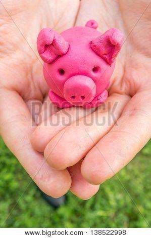 Hands holding pink piggy as moneybox. Savings concept. poster