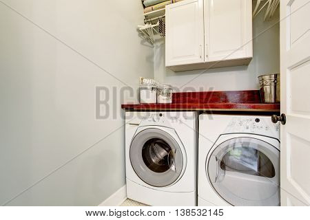 Small Laundry Room With Tile Floor, Door, And Washer Dryer Set.