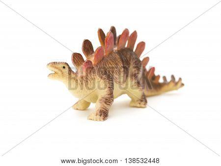 brown stegosaurus toy on a white background