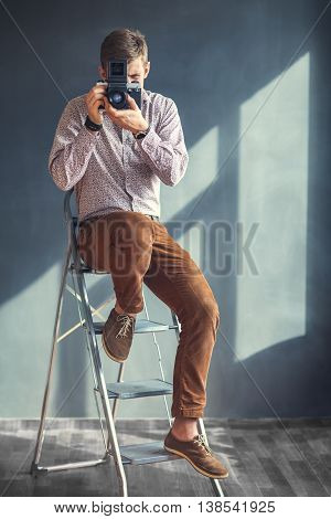 Portrait Of Handsome Man With Retro Middle Format Camera In Studio