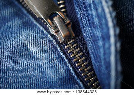 Macro detail of a metal zipper sliding on the dark blue jeans