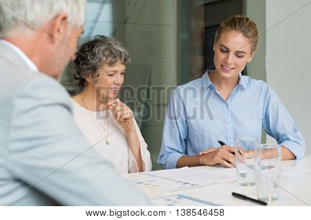 Senior businesswoman analyzing charts and graphs with her assistant and boss. Team of business people discussing during a meeting. Happy busineswoman reading report and thinking about future.