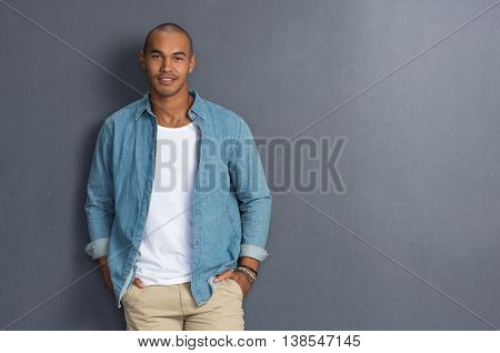 Happy young african man leaning on a grey wall with copy space. Handsome  man in casual leaning against a grey background and looking at camera. Stylish guy looking at camera with hands in pocket.