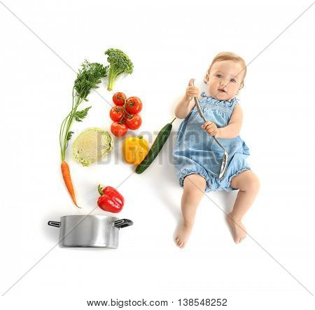 Cute baby girl with skimmer and vegetables, top view