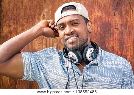 Young afro american man smiling at camera - Self confident black guy with cap staring into the eyes on wood background - Portrait of attractive african male wearing headphones