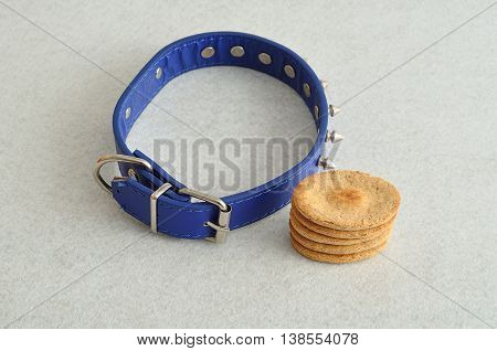 A stack of dog biscuits and a blue spike dog collar displayed on a white background
