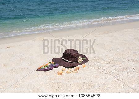 Tropical beach getaway with hat, flip flops and seashell on sandy beach