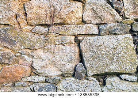 Stone wall texture made from uneven sized rocks with twigs and cobwebs in the gaps