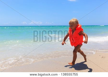 cute little girl in life jacket on summer beach, safety concept