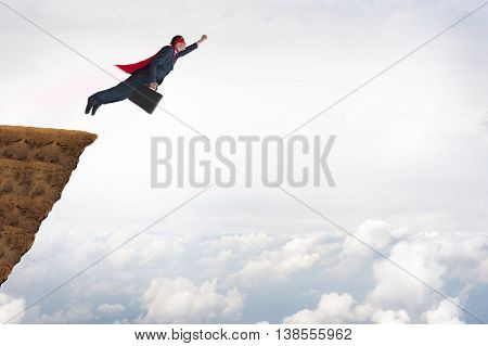 business success concept superhero businessman flying off a cliff