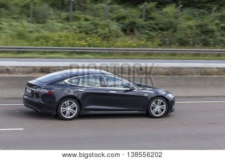 FRANKFURT GERMANY - JULY 12 2016: Black Tesla Model S luxury electric sedan on the highway in Germany