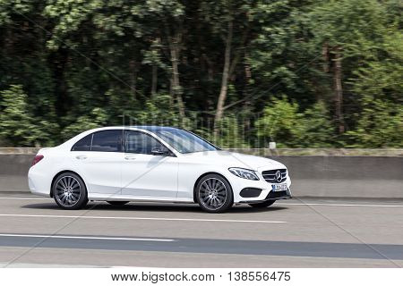 FRANKFURT GERMANY - JULY 12 2016: White Mercedes Benz C-Class luxury sedan driving on the highway in Germany