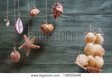 Beautiful sea composition with ship seashells starfish copy space on wooden background. Marine still life with toy model of ship made of cockleshells. Travel and adventure concept