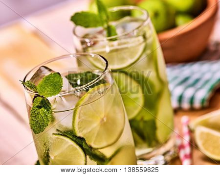 Alcohol drink. On wooden boards top of two glasses with alcohol drink and ice cubes. A drink number hundred eighty one cocktail mohito with straw. Country life.
