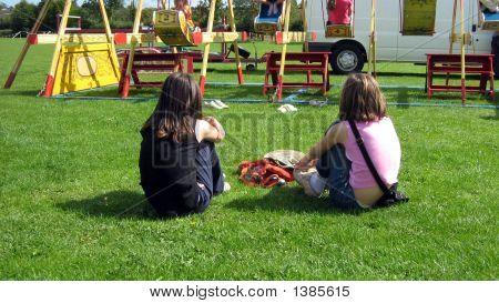 Girls Sitting On Grass Watching Swing Boats