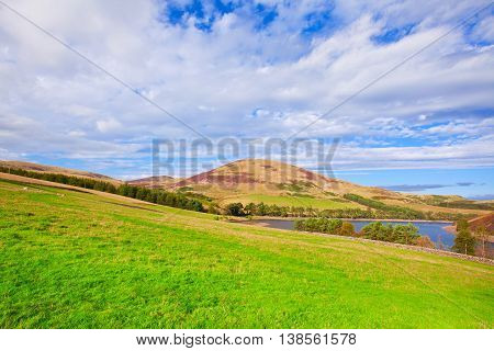 Landscape Scenery Of Green Valley, Hill, River And Cloudy Blue Sky