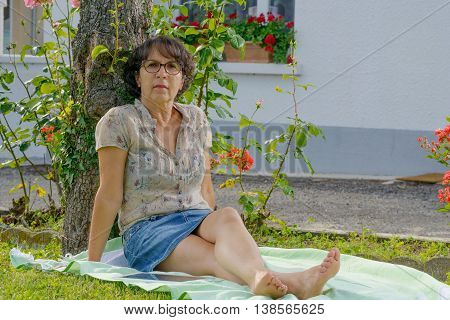 middle-aged woman with glasses is resting in the garden